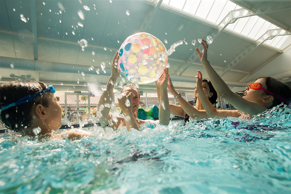 Family playing with a beach ball in swimming pool at accessible caravan park in Lothian, Scotland