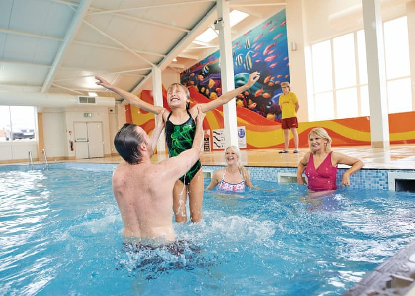Family playing in indoor swimming pool at Yorkshire holiday park