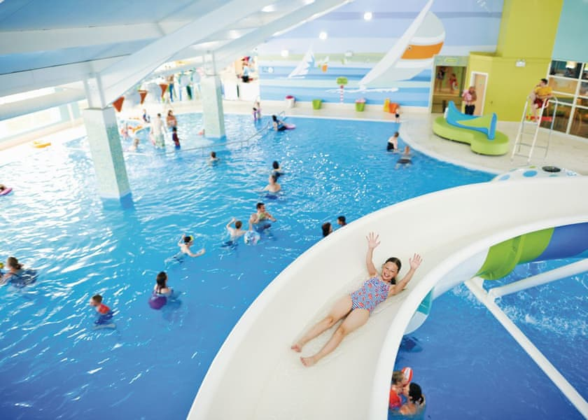 Children using a water slide in a swimming pool at a Yorkshire holiday park