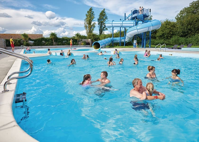 People enjoying a swimming pool with water slide at an accessible holiday park in Lincolnshire