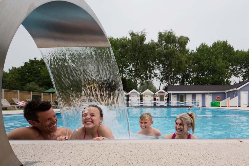 Family enjoying a swimming pool water feature in an accessible caravan park in Norfolk