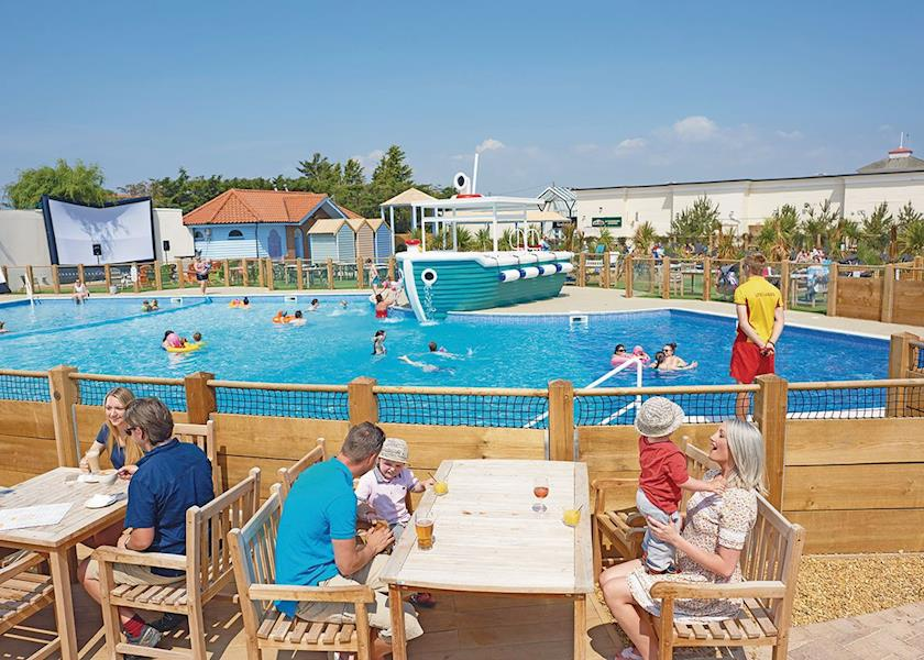 People enjoying the outdoor swimming pool at traditional Essex holiday park