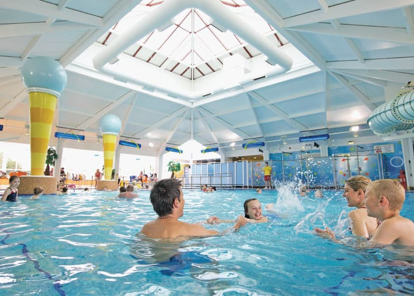 Family swimming in indoor swimming pool at accessible Sussex holiday park