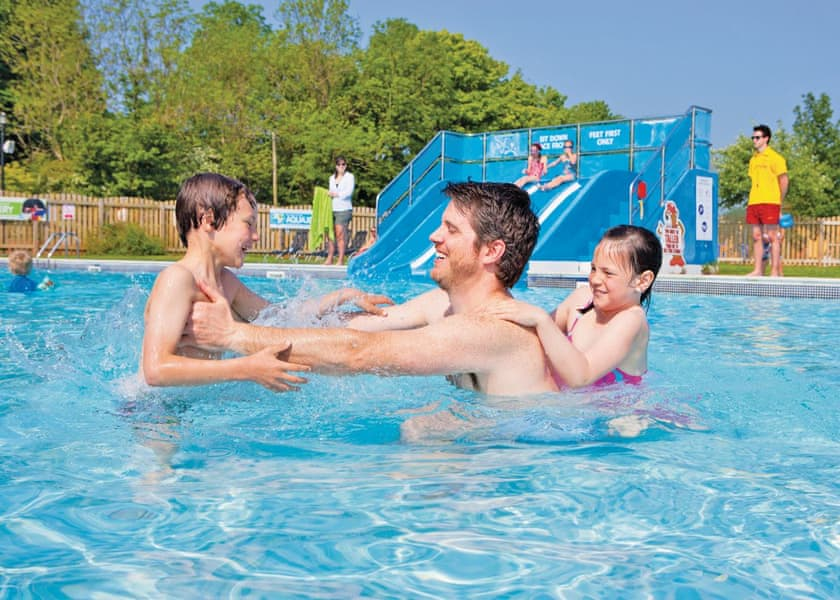 Family enjoying the swimming pool at accessible holiday park in Wales
