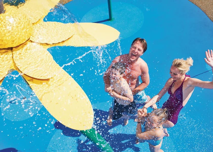 Family enjoying swimming pool Splash Zone at accessible holiday park in Wales