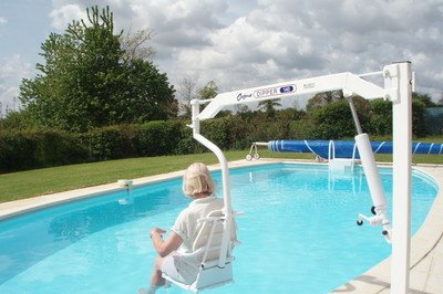 Guest using a pool hoist chair at accessible farmhouse in Normandy