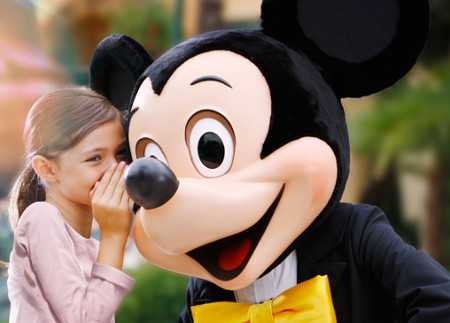Girl whispering to Mickey Mouse at Disney theme park