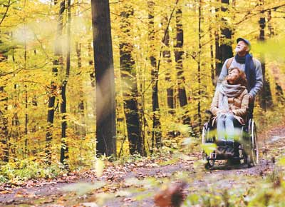 Couple walking in woods with wheelchair