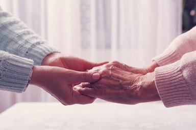 Carer holding hands with elderly patient