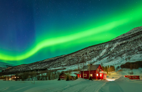 Northern Lights over a red house in the snow in northern Norway