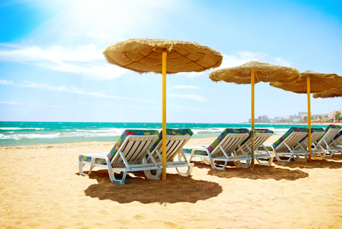 Deck chairs on a sunny beach on the Costa del Sol, Spain