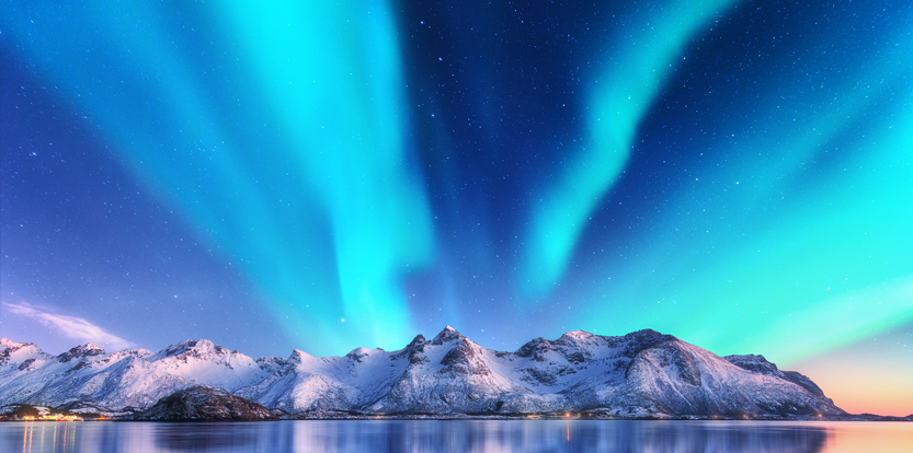 Blue Northern Lights over snowy mountains in Lofoten, Norway