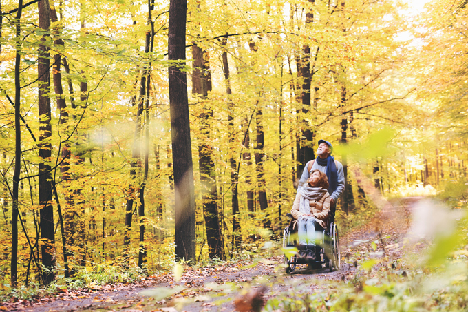 Elderly couple walking through the woods with a wheelchair
