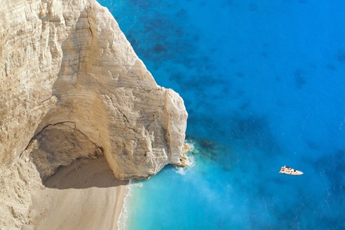 A boat on the sea next to sandy beach and cliffs in the Mediterranean.